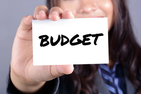 shown: BUDGET word on the card shown by a businesswoman