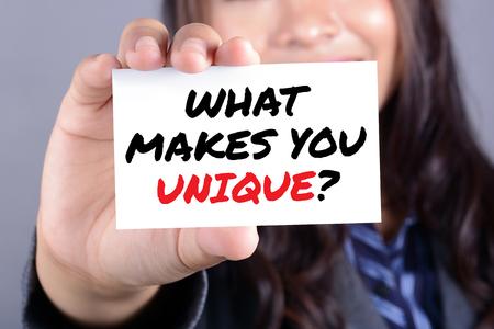 WHAT MAKES YOU UNIQUE?, message on the card shown by a businesswoman Foto de archivo