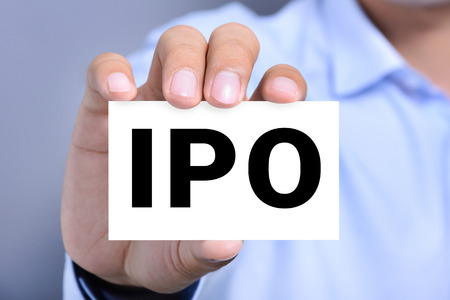 initial public offerings: IPO letters  (or Initial Public Offering) on the card held by a man hand Stock Photo