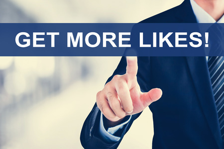 likes: Businessman hand touching GET MORE LIKES! message on virtual screen Stock Photo