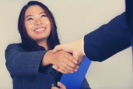 handclasp: Young Asian businesswoman making handshake, vintage tone
