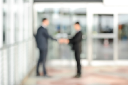 blurred background: Blurred image of businessmen making handshake in front of office building doors, can be used as background