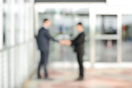 handshake: Imagen borrosa de los hombres de negocios haciendo apret�n de manos delante de las puertas del edificio de oficinas, se puede utilizar como fondo