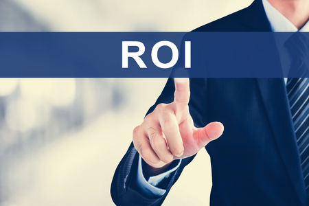 return on investment: Businessman hand touching  ROI (or RETURN ON INVESTMENT) tab on virtual screen