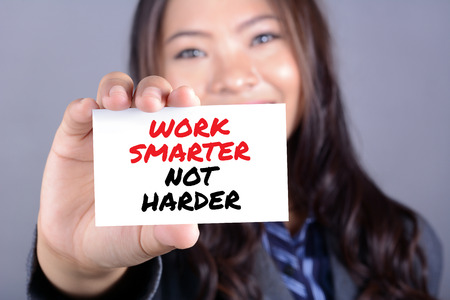 harder: Businesswoman showing card with a message WORK SMARTER NOT HARDER Stock Photo
