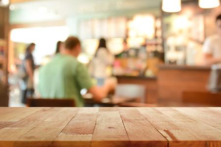 Holztischplatte auf Blur Hintergrund der Café-Interieur mit einigen Menschen - kann zur Anzeige oder verwendet montage Ihre Produkte werden Lizenzfreie Bilder