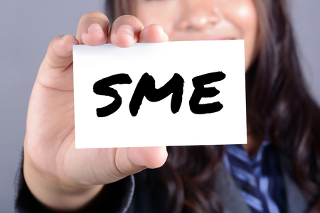 enterprises: SME letters (or Small and Medium-sized  Enterprises) on the card shown by a businesswoman Stock Photo
