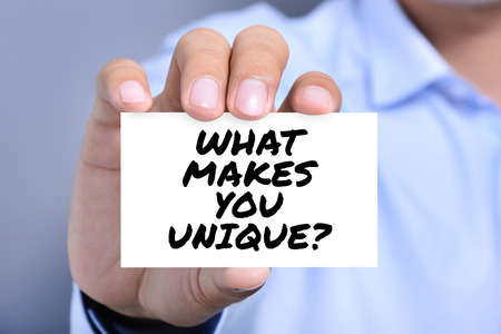 WHAT MAKE YOU UNIQUE? message on the card shown by  a man
