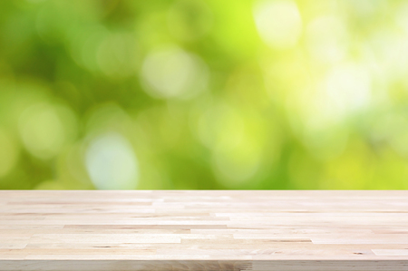 wooden boards: Wood table top on bokeh abstract green background  - can be used for montage or display your products Stock Photo
