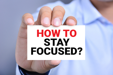 how: HOW TO STAY FOCUSED? message on the card shown by a man