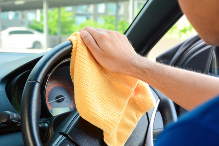 valeting: A man hand cleaning car steering wheel with microfiber cloth, auto detailing (valeting) concept