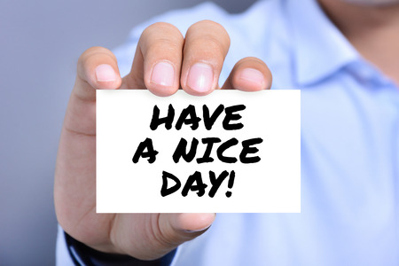 nice guy: HAVE A NICE DAY! message on the card shown by a man