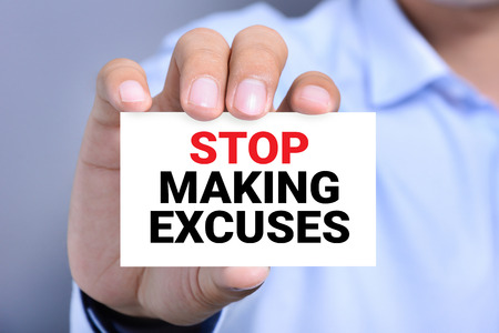 making notes: STOP MAKING EXCUSES message on the card shown by a man