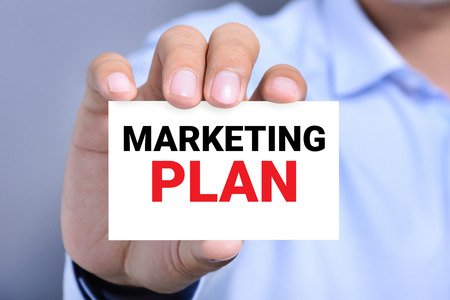 MARKETING PLAN message on the card shown by a man Foto de archivo