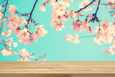 Wood table top on blur pink Sakura flower background, vintage tone - can be used for display or montage your products Stock Photo