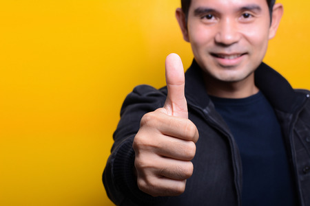 Young man with smiling face giving thumbs up on yellow background