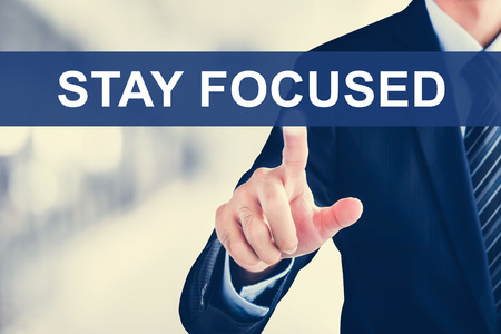 staying: Businessman hand touching  STAY FOCUSED sign on virtual screen