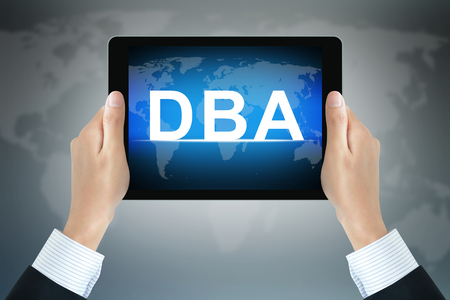 graduate: DBA (or Doctor of Business Administration) sign on computer tablet screen held by businessman hands