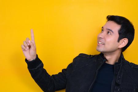 visage homme: Jeune homme asiatique regardant et pointant espace vide avec un visage souriant sur fond jaune