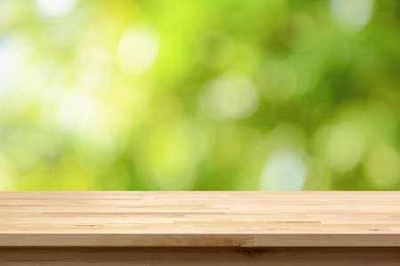 Wood table top on natural green bokeh abstract background - can be used for display or montage your products Imagens