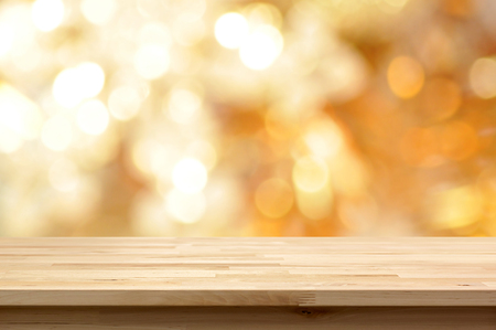 defocused: Wood table top on golden bokeh abstract background  - can be used for montage or display your products Stock Photo