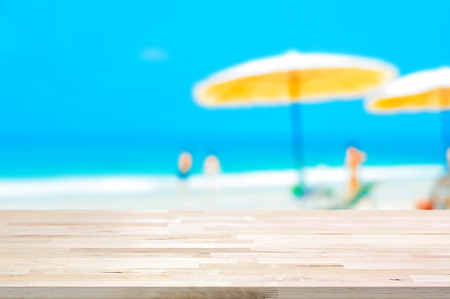 holiday display: Wood table top on blurred beach background, summer holiday background concept  - can be used for montage or display your products