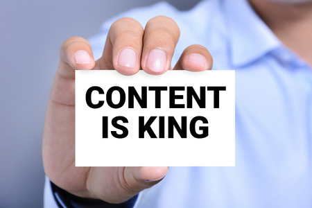 news values: CONTENT IS KING message on the card shown by a man Stock Photo