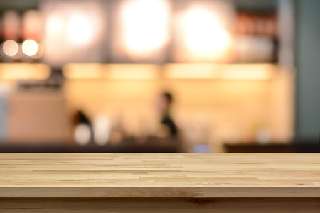 Wood table top on blur cafe ( coffee shop) interior background - can be used for display or montage your products Standard-Bild