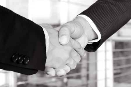 mergers: Handshake of businessmen in black and white tone - greeting, dealing, mergers and acquisition concept Stock Photo
