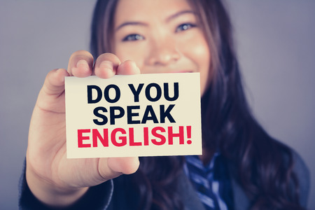 speak: DO YOU SPEAK ENGLISH! , message on the card shown by a young woman