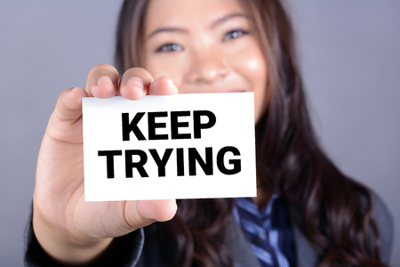 trying: KEEP TRYING,message on the card shown by a businesswoman