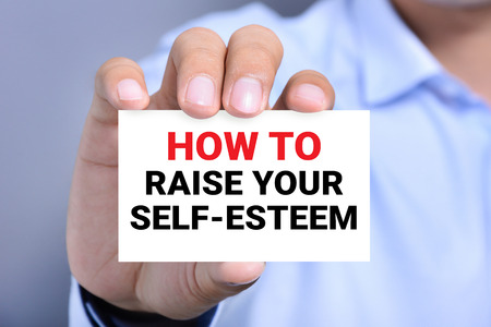 self worth: HOW TO RAISE YOUR SELF-ESTEEM, message on the card shown by a man Stock Photo