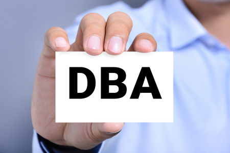 administracion empresarial: DBA letters (or Doctor of Business Administration) on the card shown by a man