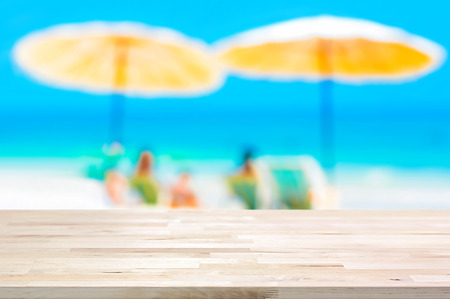 blurred background: Wood table top on blurred beach background, summer holiday background concept  - can be used for montage or display your products