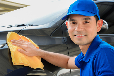 cleaning service: A man with smiling face cleaning car