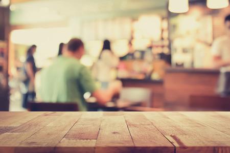 Houten tafelblad op onscherpte achtergrond van koffieshop interieur met een aantal mensen, vintage toon - kan worden gebruikt voor weergave of Montage uw producten