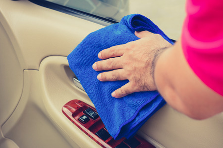 valeting: Hand cleaning interior car door panel with microfiber cloth