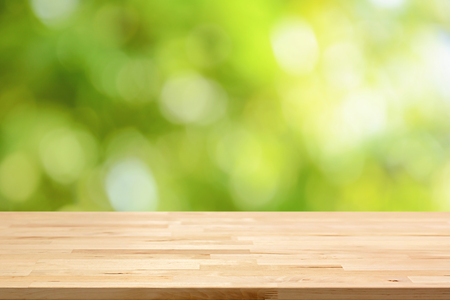 yellow green: Wood table top on green bokeh abstract background - can be used for montage or display your products