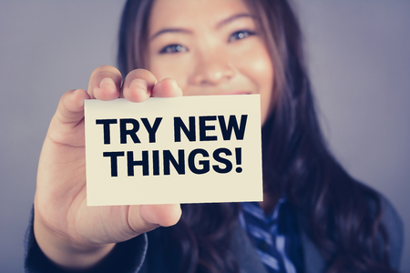 try: TRY NEW THINGS! messsage on the card shown by a businesswoman