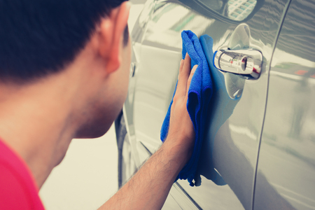 A man cleaning car with microfiber cloth Stock Photo