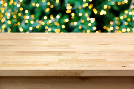 empty table: Wood table top on blur bokeh background from decorative light on Christmas tree - can be used for display or montage your products