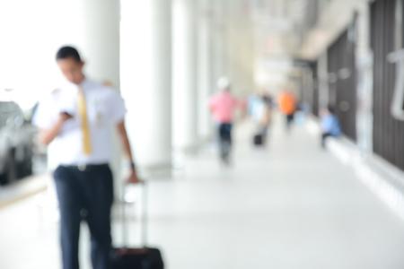 flight crew: Blur image of flight crew and people walking in airport corridor