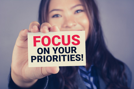 FOCUS ON YOUR PRIORITIES! , message on the card shown by a businesswoman