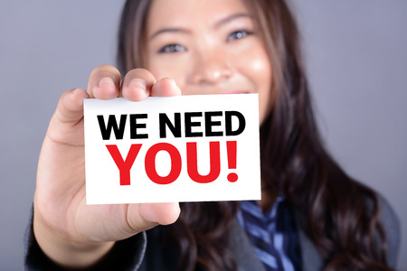WE NEED YOU! message on the card shown by a businesswoman