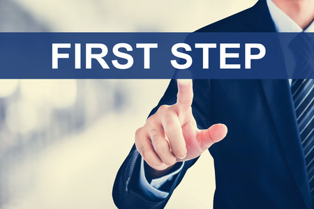 step by step: Businessman hand touching FIRST STEP tab on virtual screen Stock Photo