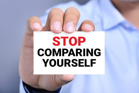 morale: STOP COMPARING YOURSELF, message on the card shown by a man