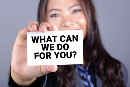 WHAT CAN WE DO FOR YOU? message on the card shown by a businesswoman 스톡 콘텐츠