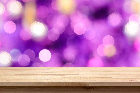 Wood table top on colorful purple bokeh abstract background - can be used for montage or display your products