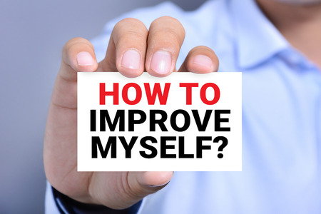self development: HOW TO IMPROVE MYSELF? message on the card shown by a man Stock Photo