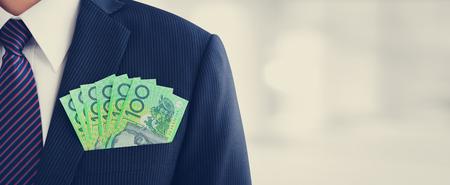 bolsa dinero: El dinero, dólar australiano (AUD) los billetes de banco, en hombre de negocios traje de bolsillo - de fondo panorámica financiera y de inversión, con copia espacio